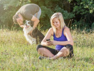 Mann streichelt Hund Frau sitzt im Gras und spielt mit dem Handy