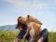 Eine junge Frau umarmt ihren Collie mitten auf einer grünen Wiese